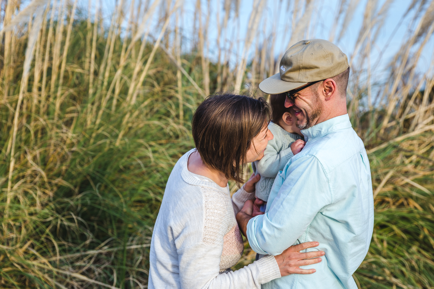 Portrait of family of three snuggling together on the beach {East Bay Family Photographer}