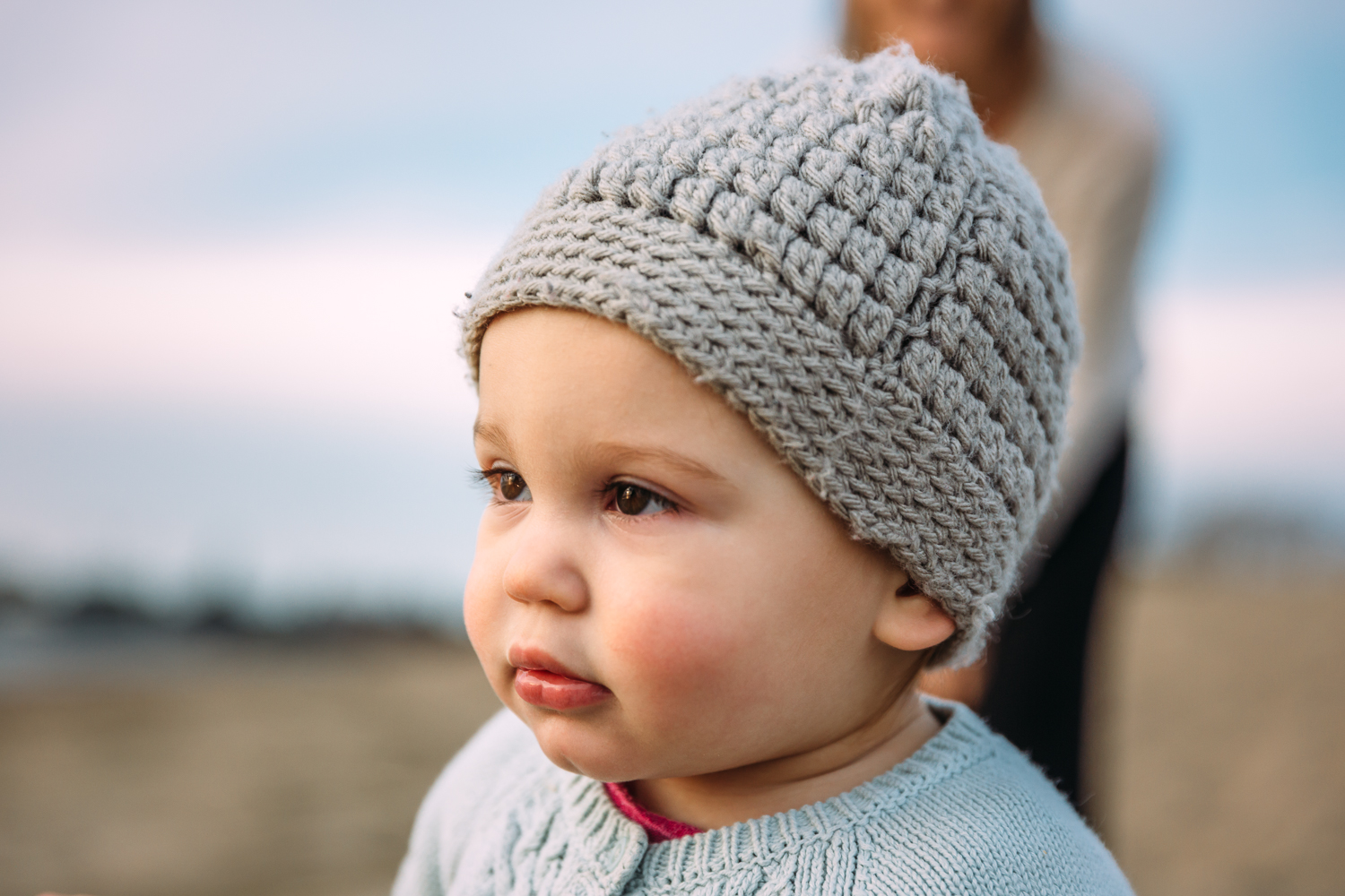 portrait of a one year oldbaby with her hat on on the beach {East Bay Baby Photographer}