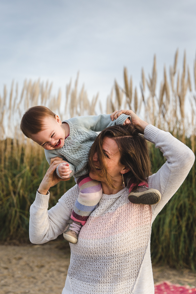 Mom holding her one year old baby on her shoulders as they both laugh {East Bay Baby Photographer}