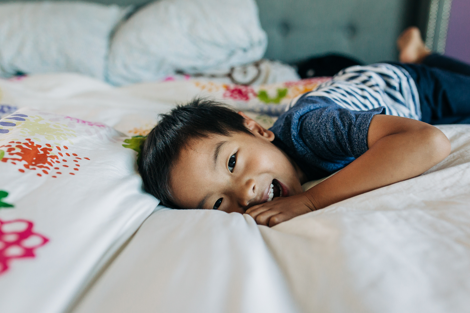 boy laying on a bed and looking and smiling at the camera | East Bay Lifestyle Family Photographer