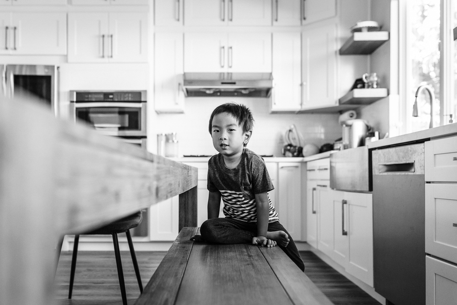 four year old boy sitting on a bench in the kitchen looking at the camera | East Bay Lifestyle Family Photographer