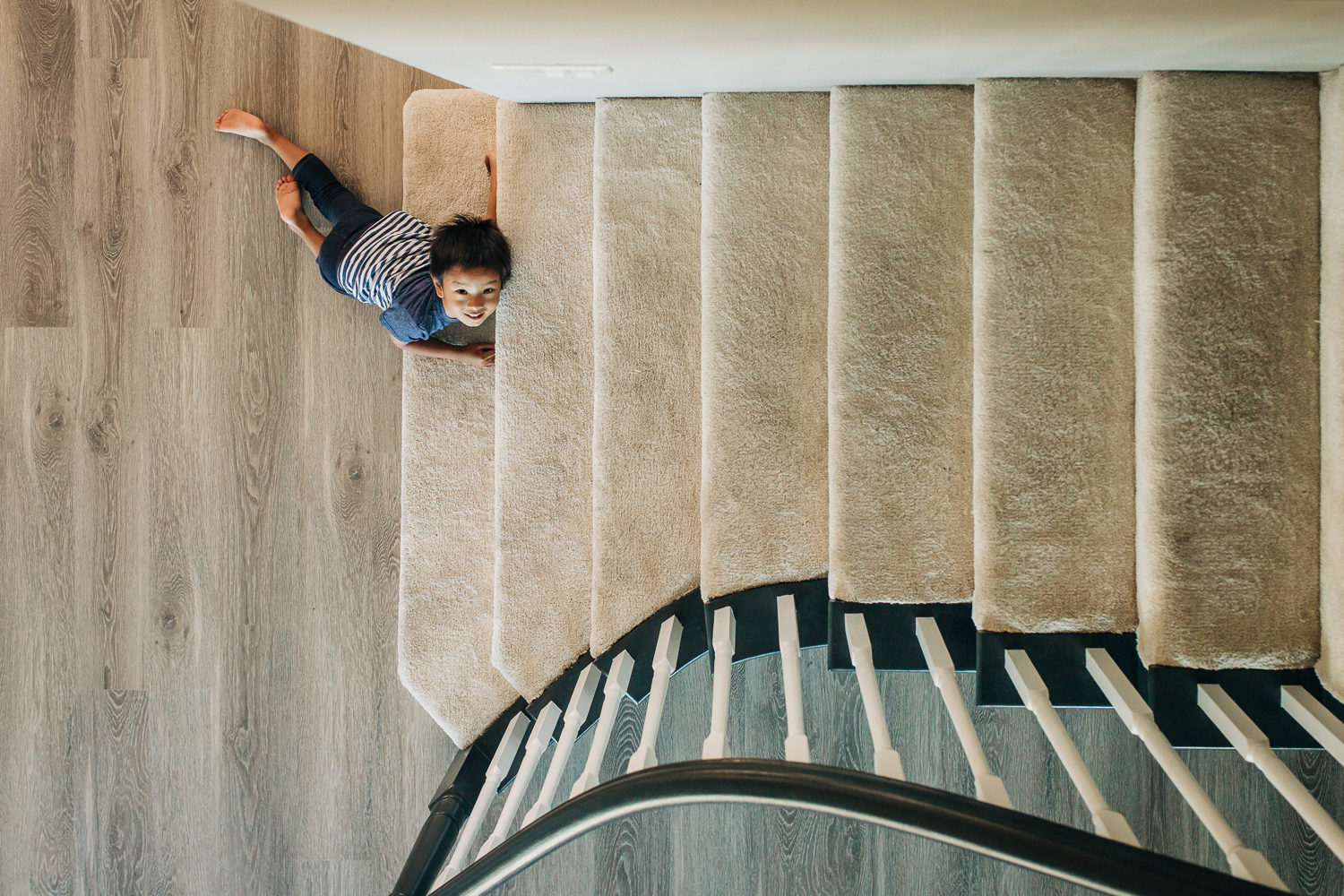 birds eye view of four year old boy as he lays at the bottom of the steps | East Bay Lifestyle Family Photographer