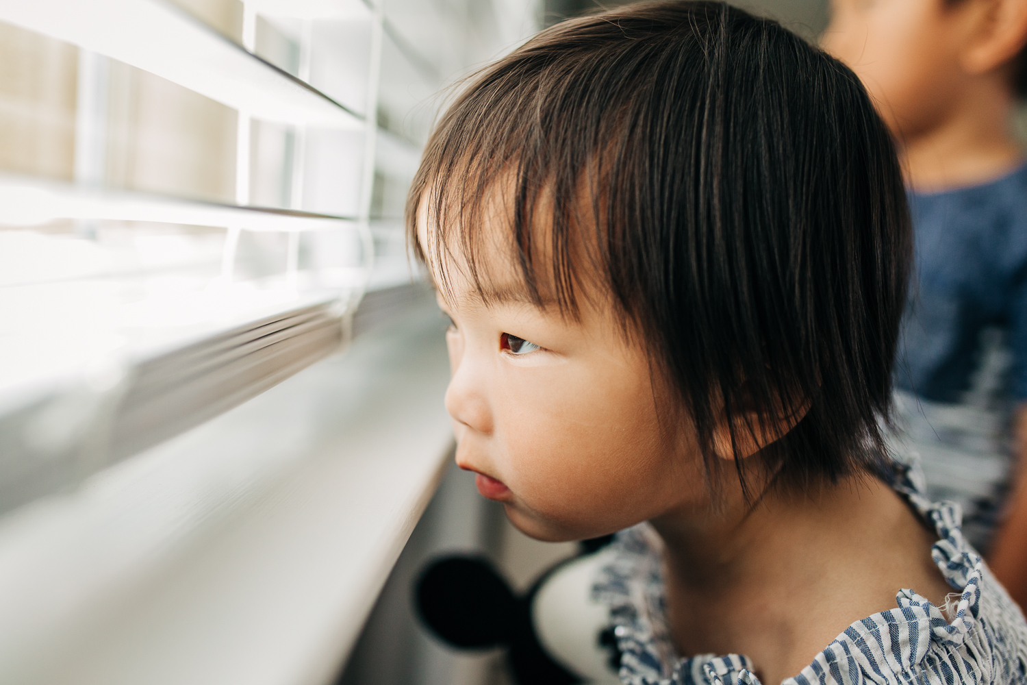 2 year old girl looking out blinds in a window {East Bay in-home lifestyle family photographer}