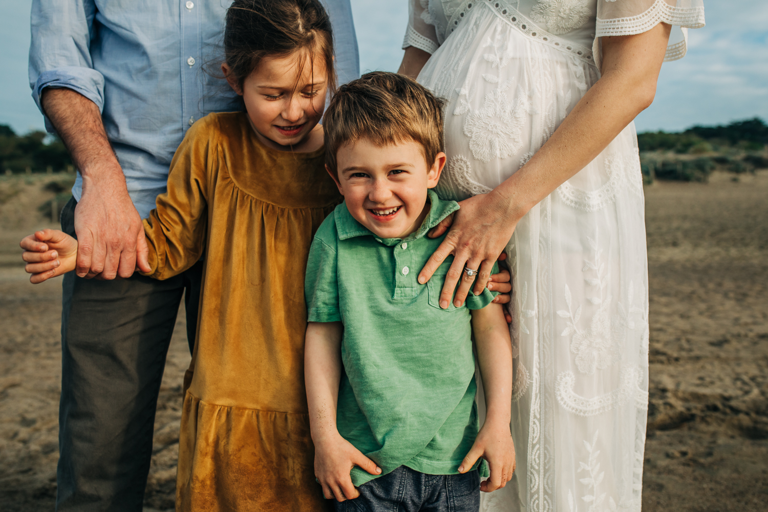 little boy smiling at the camera while standing with his family and pregnant mom at the beach | Bay Area Maternity Photographer