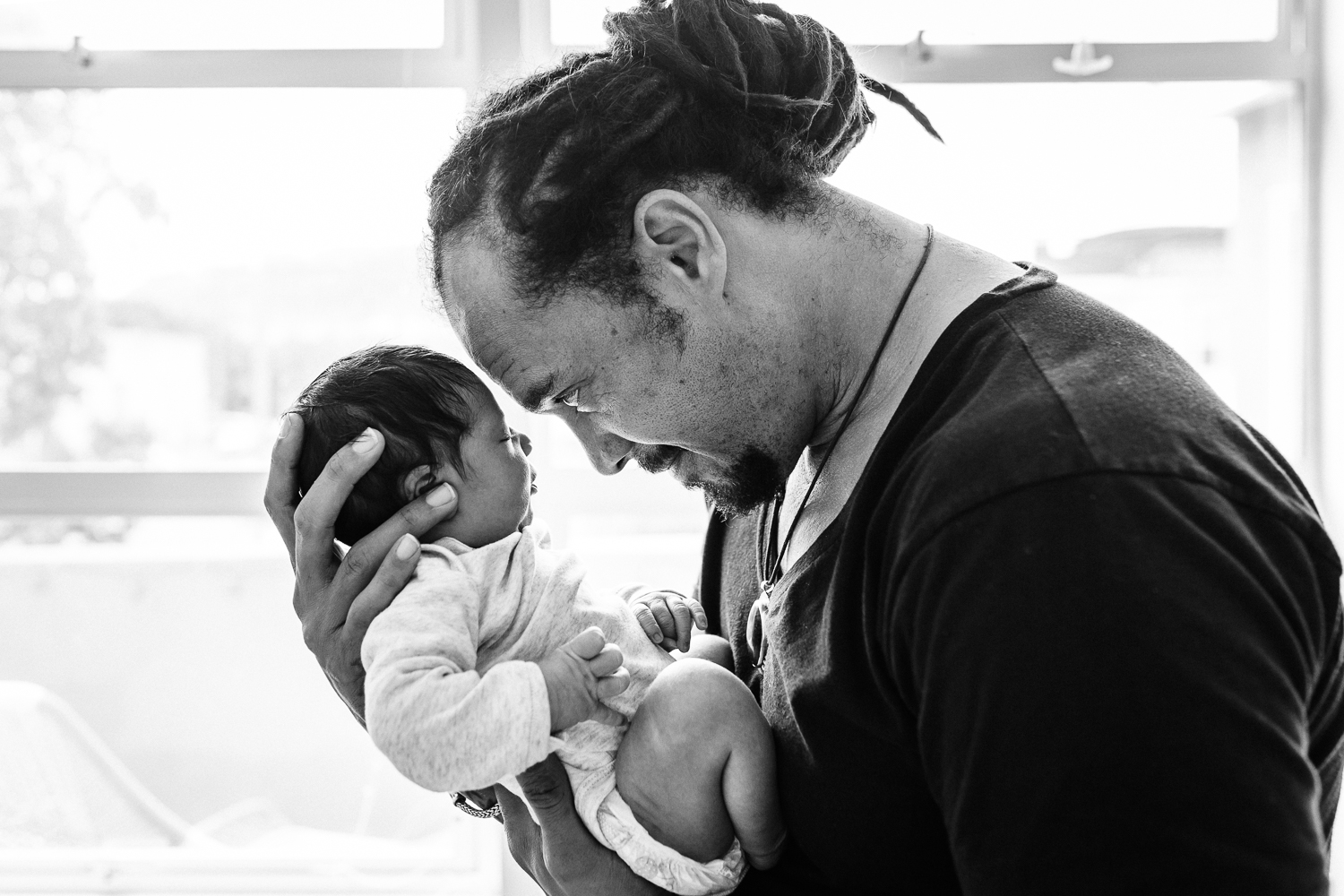 black and white shot of father holding his newborn baby boy to his forehead while standing in front of a window | San Francisco Fresh 48 Photographer