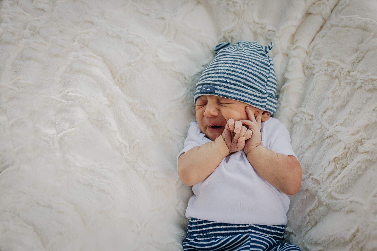 newborn boy laying down on a white blanket with his hands up by his face | SF Baby Photography