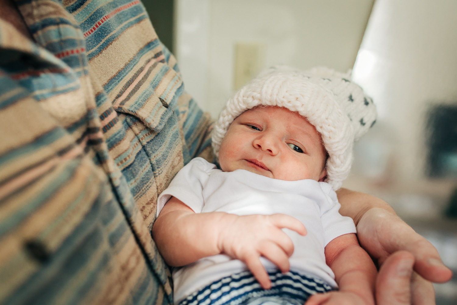 one week old baby boy in dad's arms looking towards camera while wearing a hat | SF Newborn Photographer