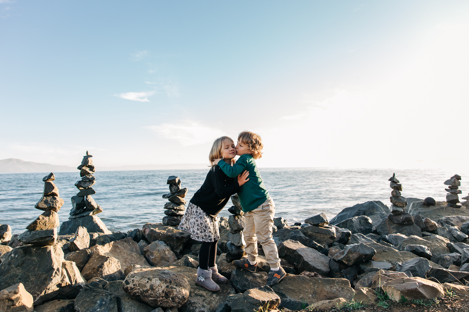 4 year old brother and 6 year old sister standing on rocks by the San Francisco Bay and hugging each other | Bay Area Family Photography
