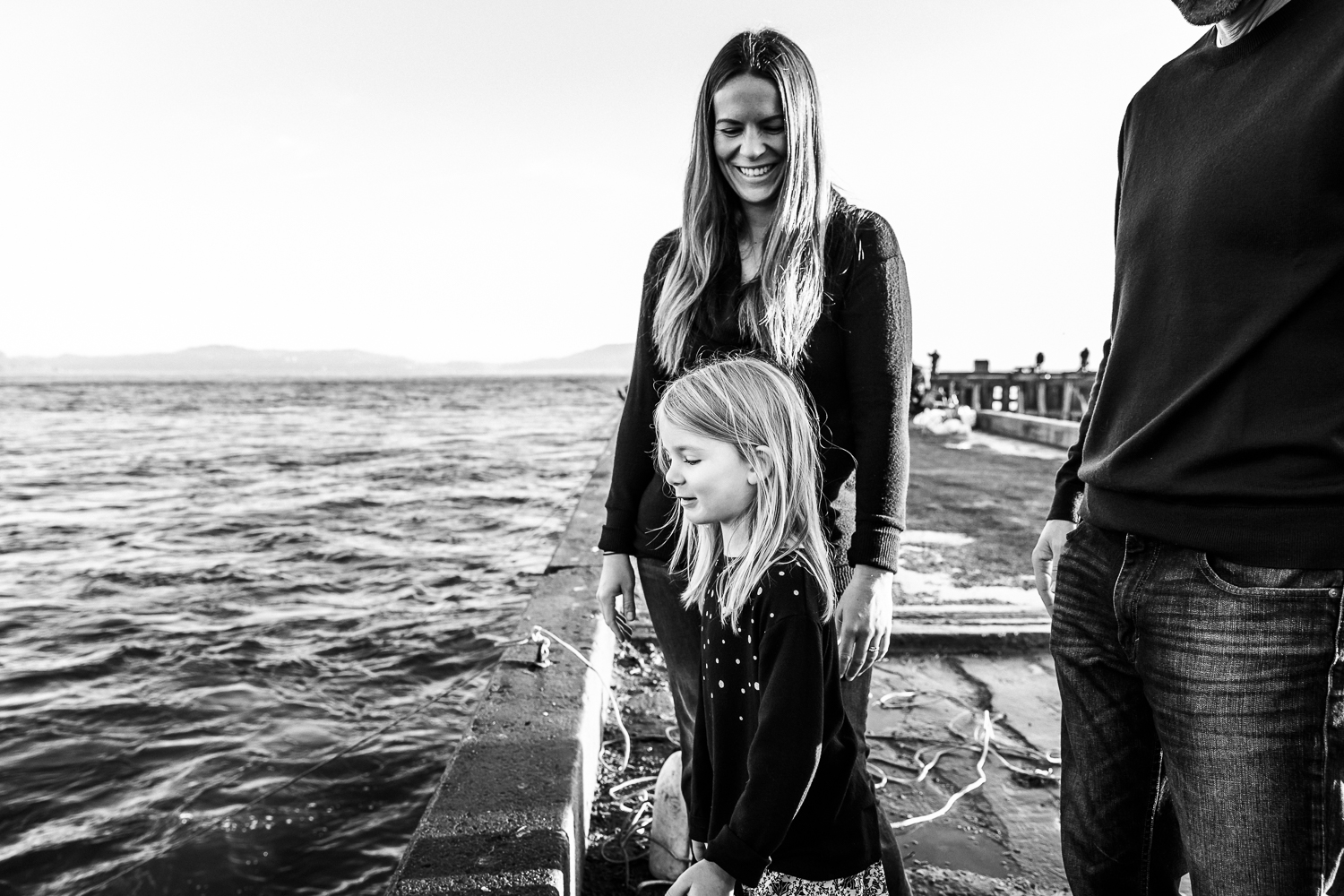 black and white shot of mom looking down at her daughter and smiling as her daughter looks in the water for fish while standing on a pier | San Francisco Portrait Photographer