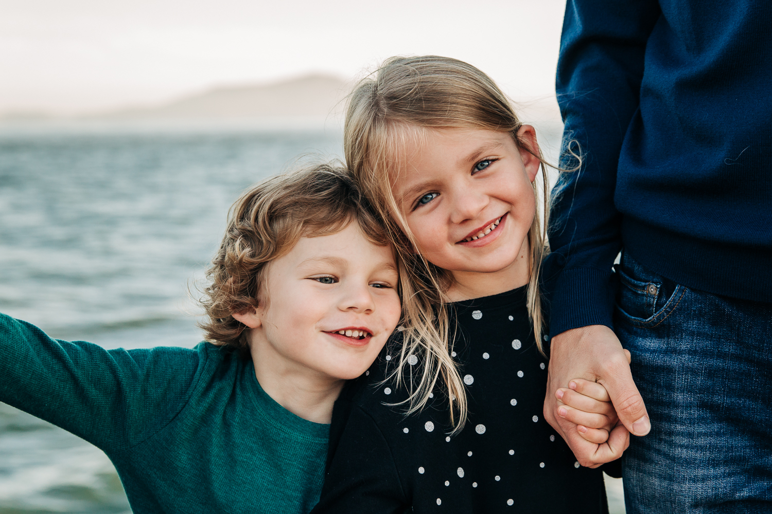 portrait of 4 year old brother and 6 year old sister snuggling while the little sister holds dad's hand | SF Bay Area Child Photographer