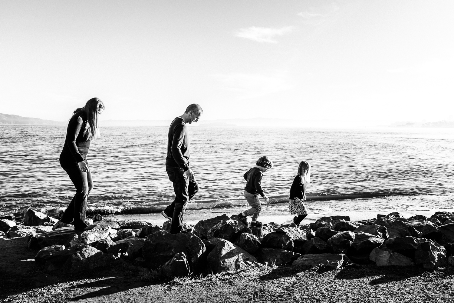 black and white photo of a family of 4 walking along rocks by the San Francisco Bay  | SF Family Photography
