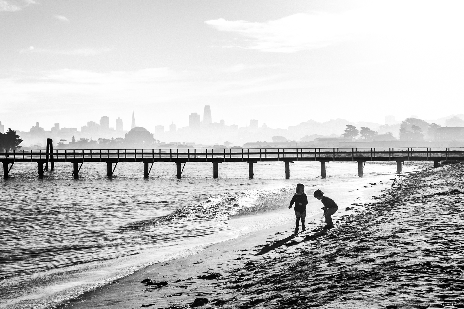 two children playing on the beach with the San Francisco skyline in the background | Bay Area Family Photographer