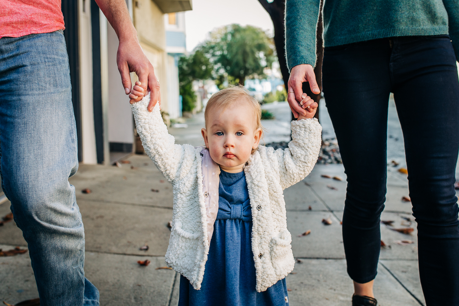 Baby walking down the street holding her parents hands | San Francisco Photographer