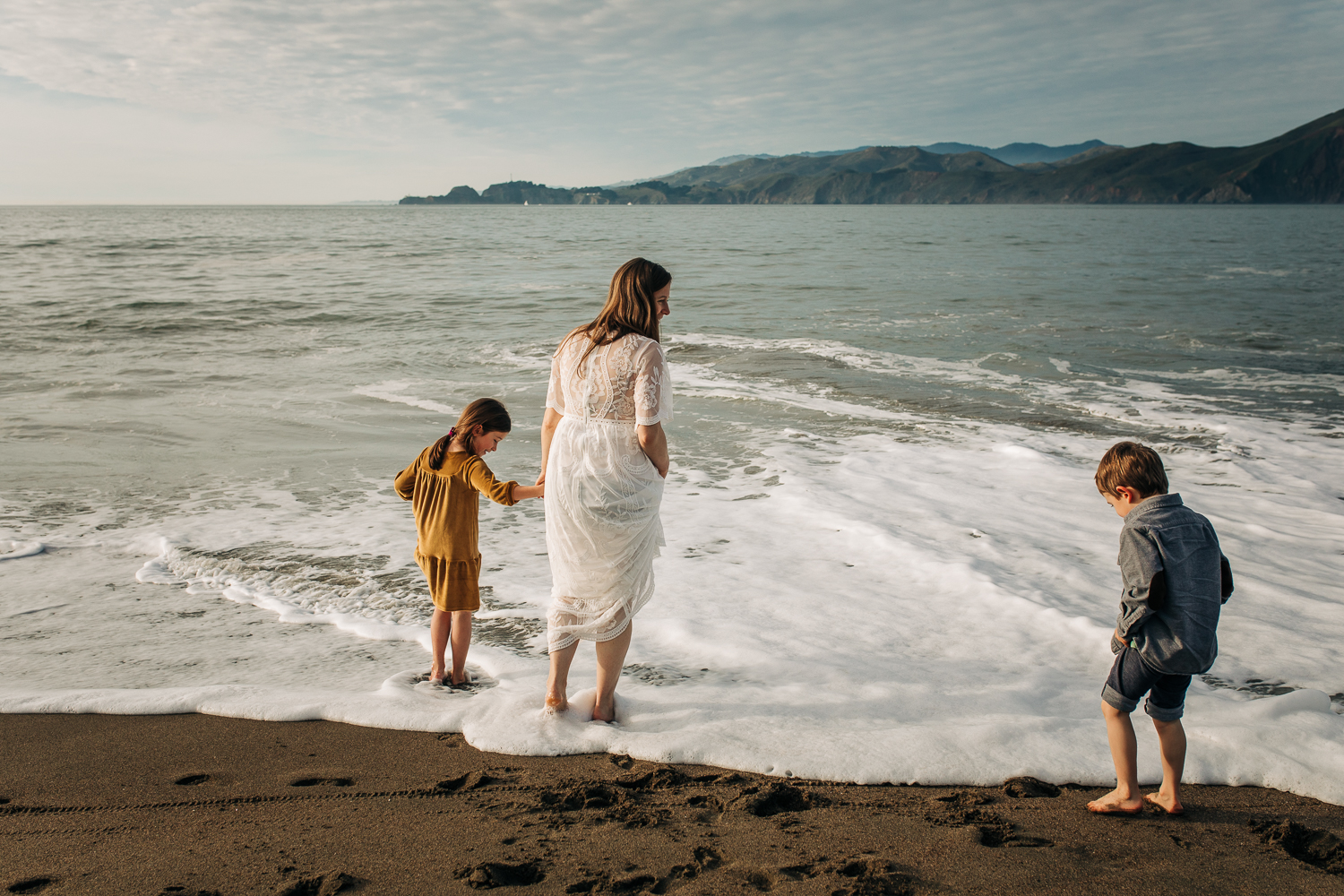 Pregnant mom playing at the beach in the water with her two children while wearing a white flowing dress | SF Maternity Photographer