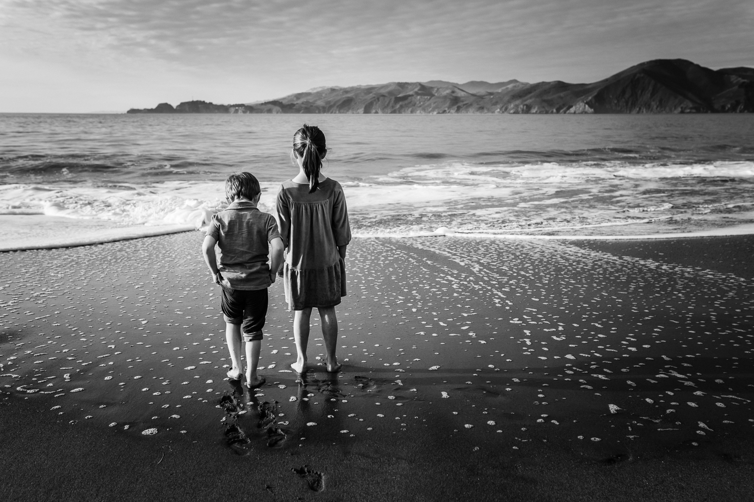 black and white photo taken from behind of two small children looking out at the ocean while standing on the beach | Bay Area Family Photographer