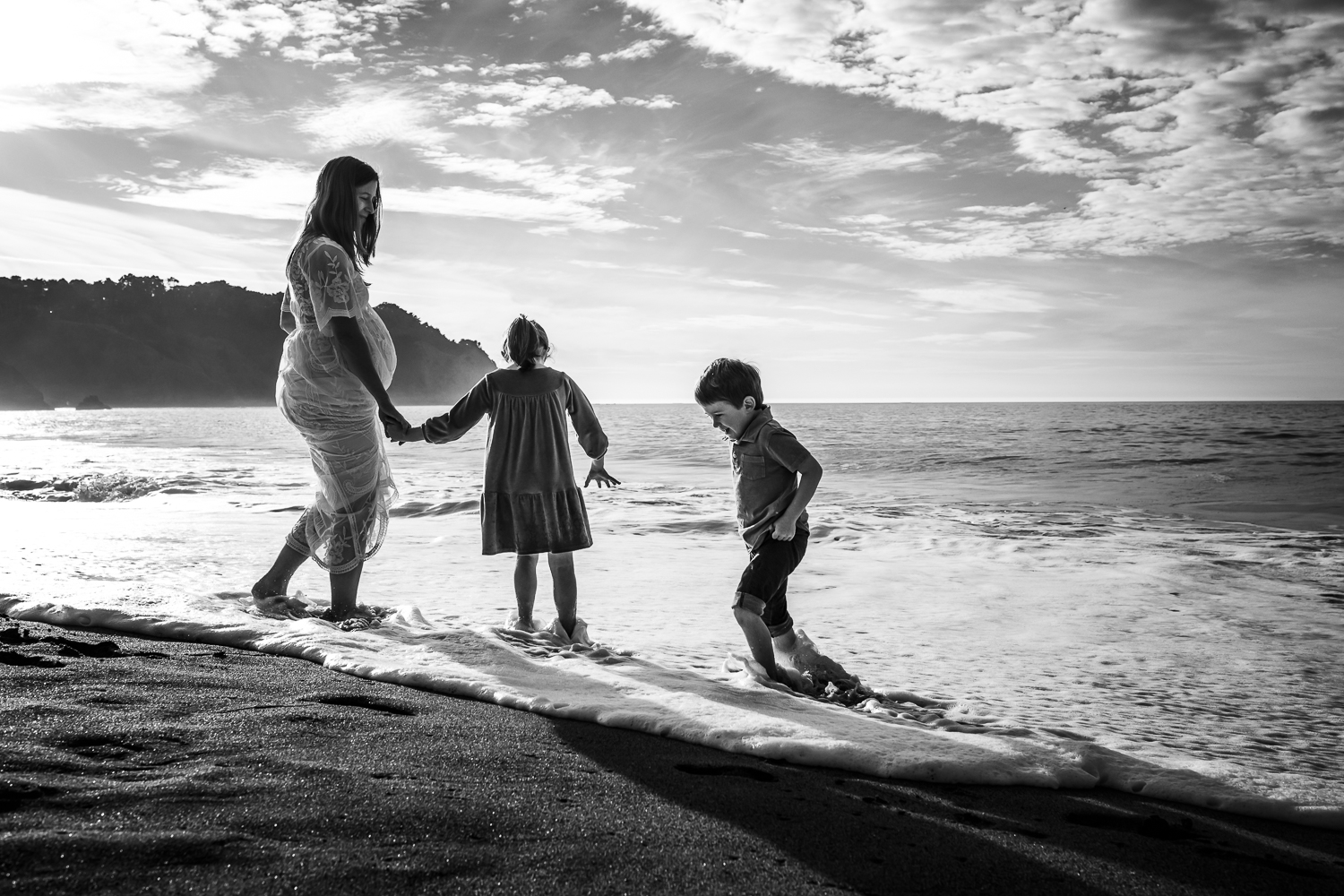 black and white photo of two small children playing in the water at the beach with their pregnant mother who is wearing a long white dress | SF Maternity Photography