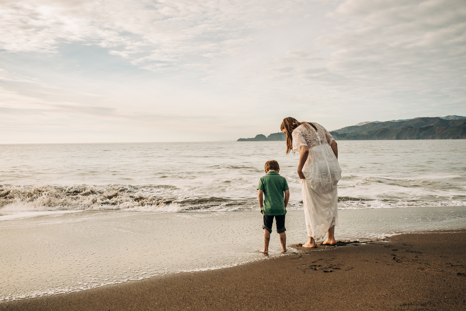 pregnant mother wading in the ocean at the beach with her toddler son | Bay Area Maternity Photographer