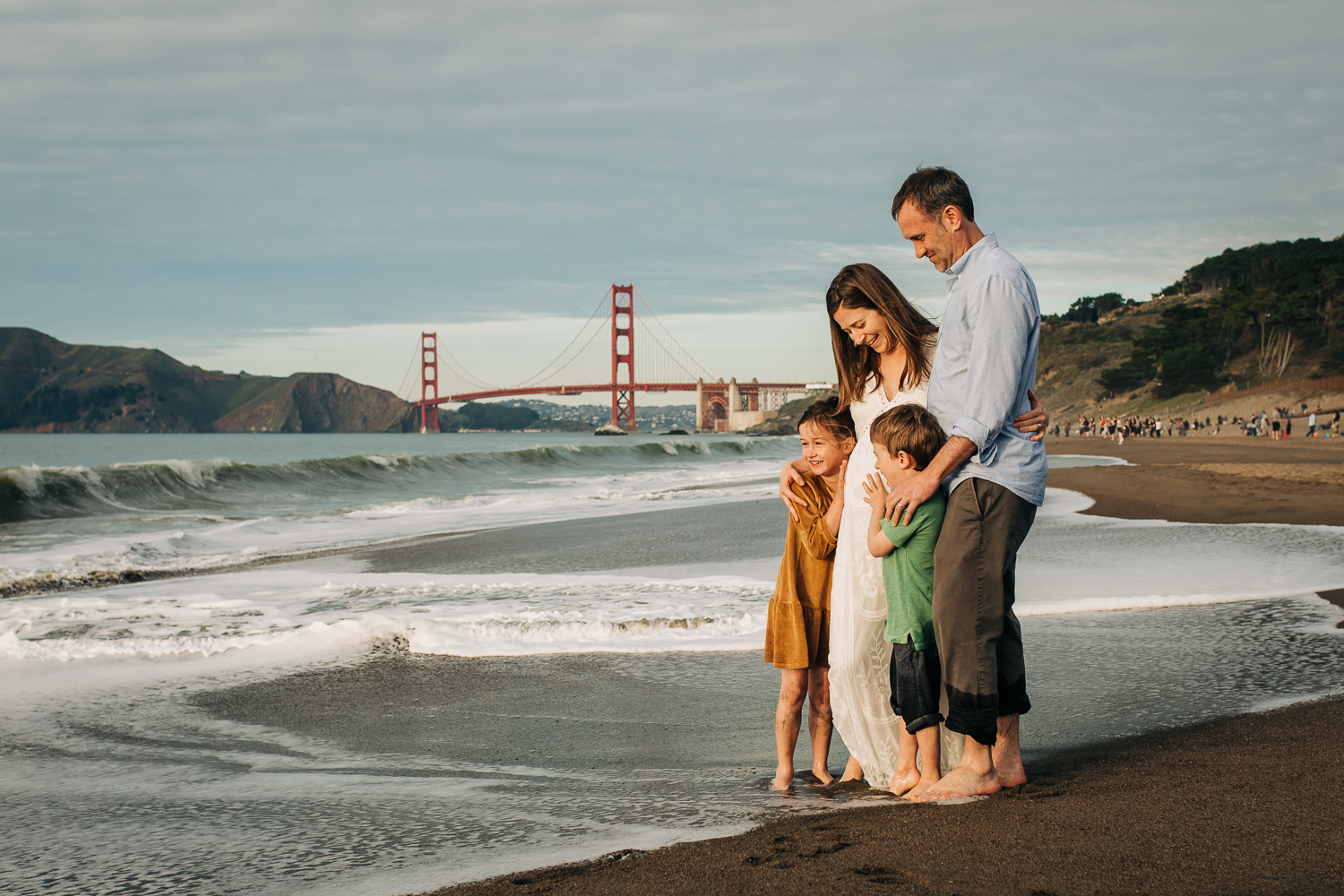 Family Portrait of a boy and a girl with both parents standing at Baker beach with the Golden Gate Bridge in the background | San Francisco Family Photography