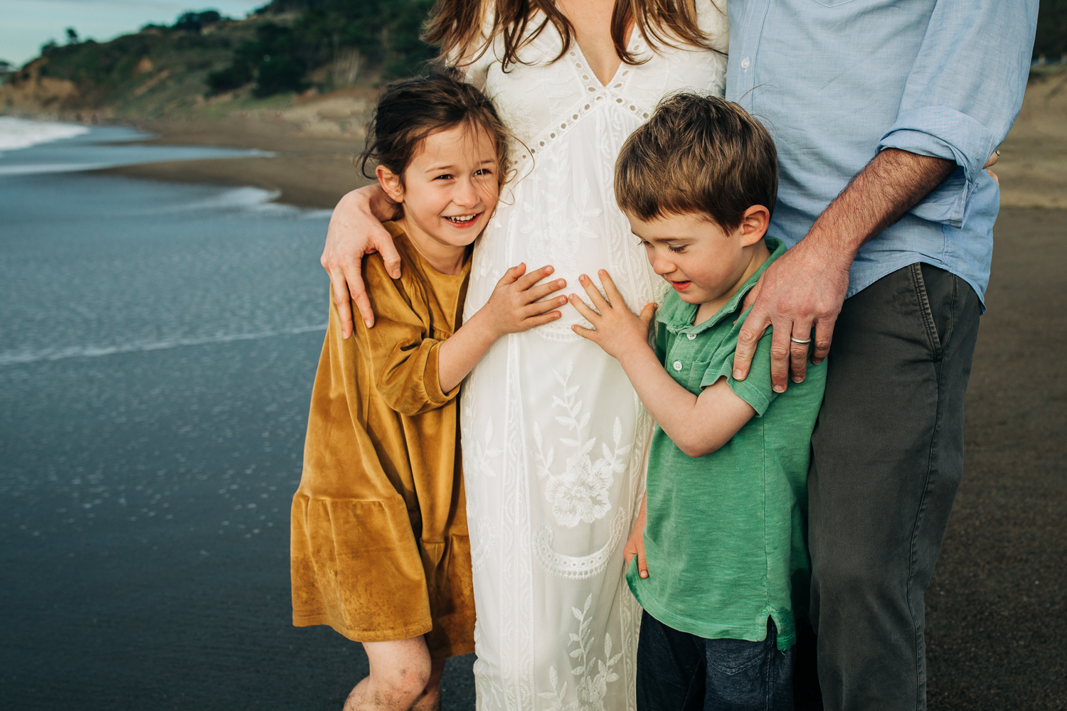 a boy and a girl standing in front of their parents with their hands on their mother's baby bump | Easy Bay Maternity Photographer