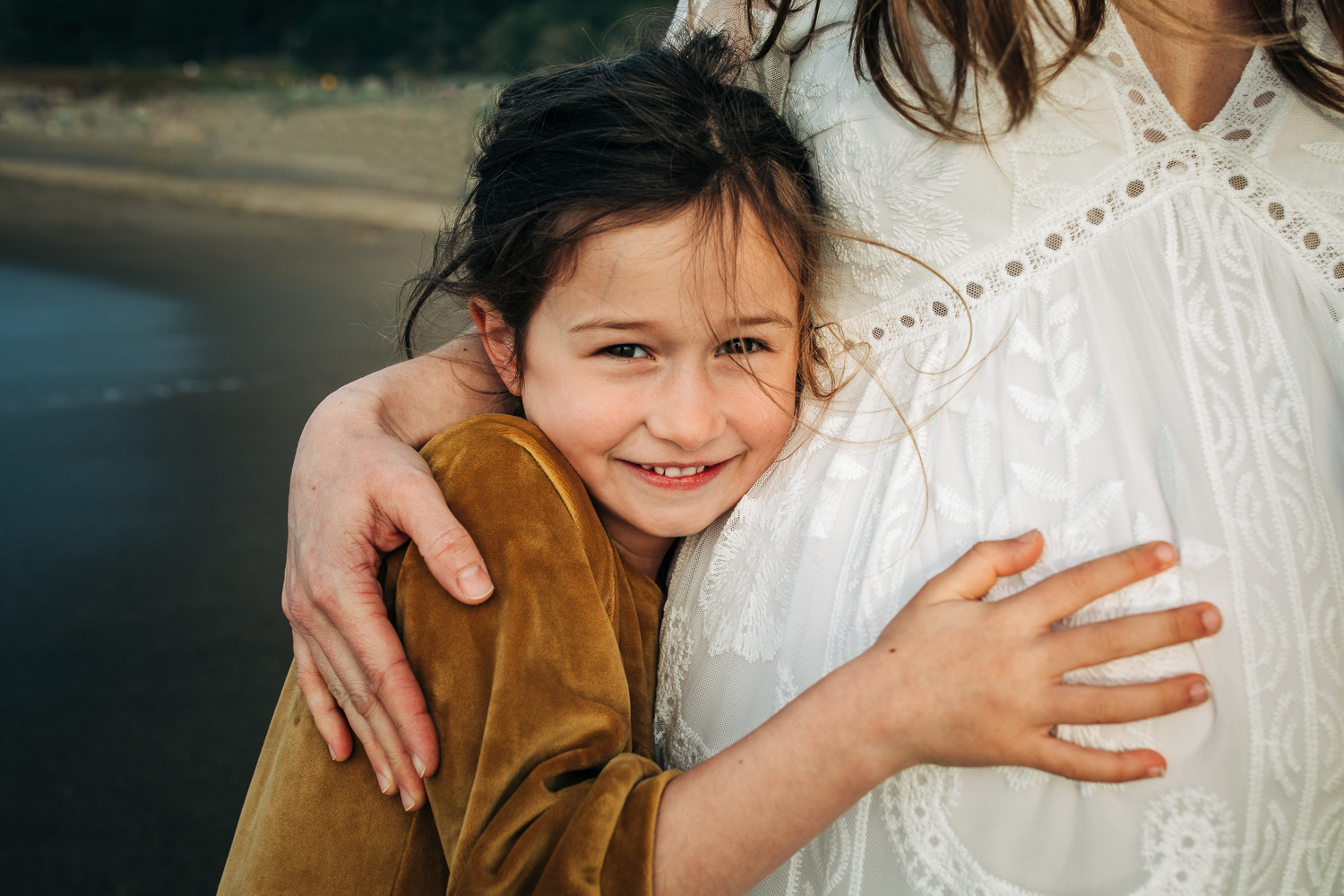 little girl smiling at the camera and snuggling her pregnant mother close and touching her mother's baby bump | San Francisco Baby Photographer