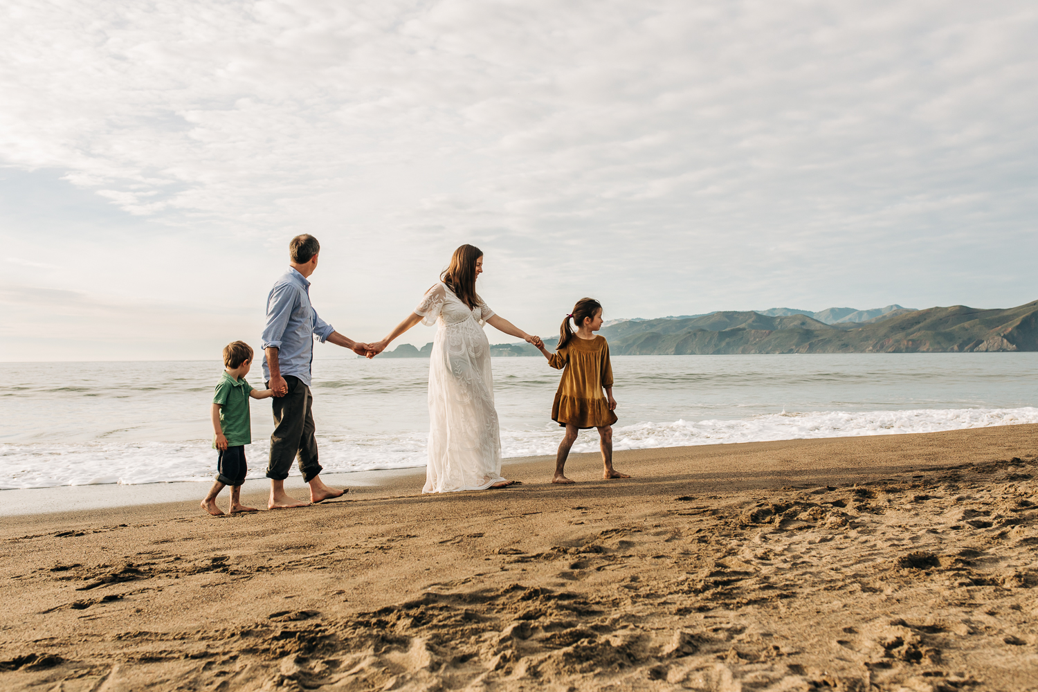 Profile of family of four with pregnant mom all walking on beach holding hands | Bay Area Maternity Photographer
