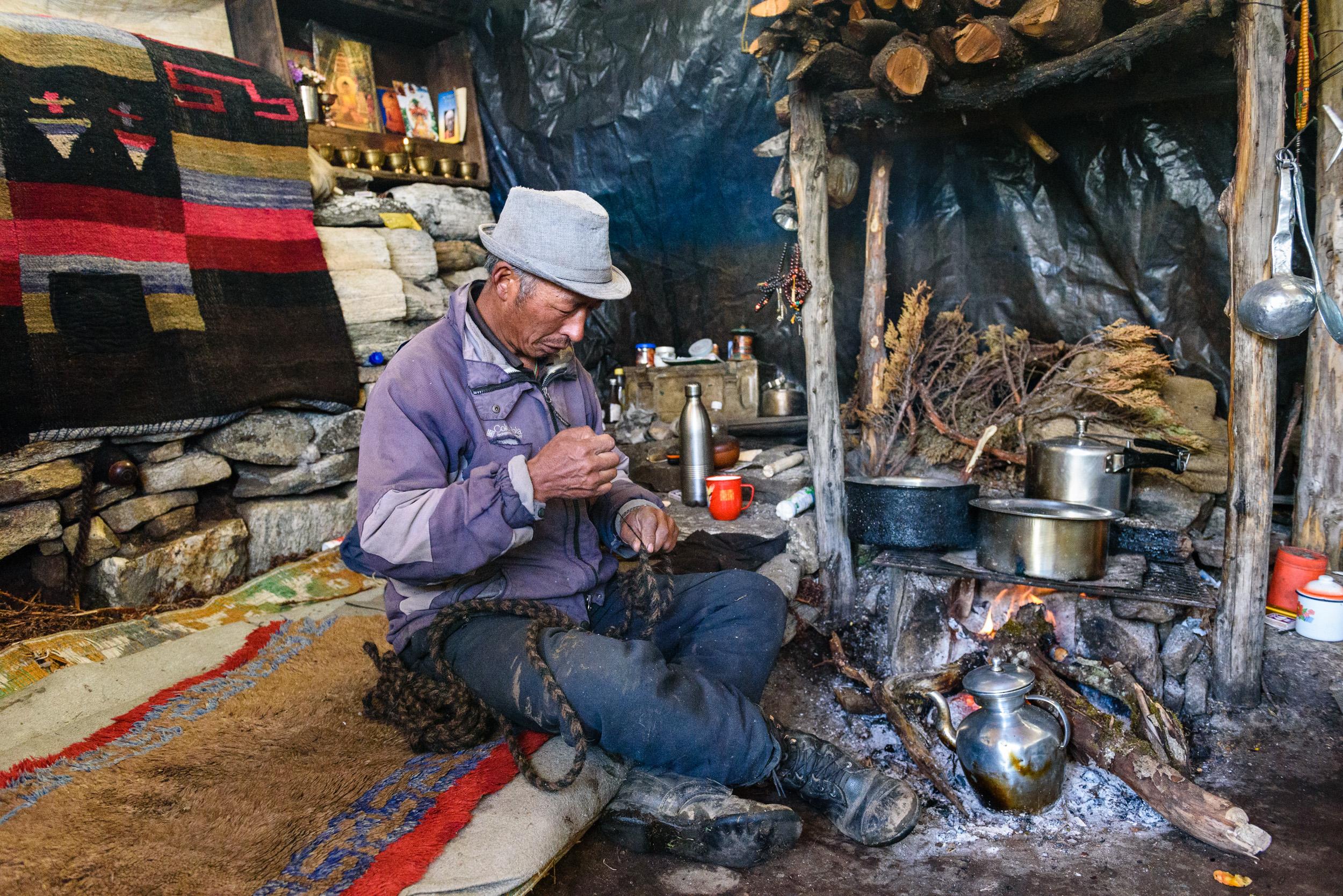Dugya inside the hut, making a yak-hair rope.