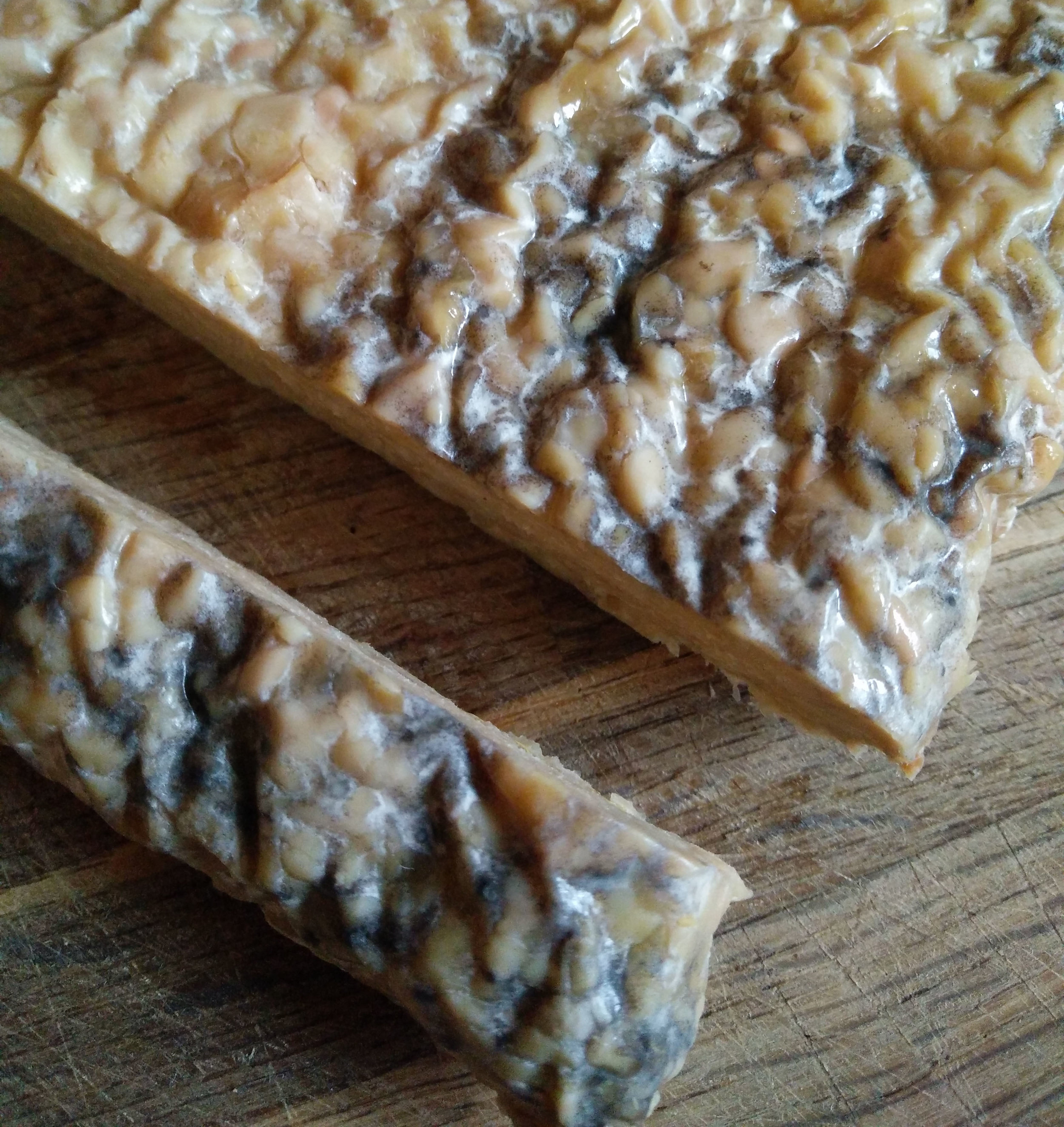 Why has my tempeh got black spots on it? - We get asked this question a lot, while most of the products we send out has the pale brown colour that you are probably used to sometimes grey patches and black spots can sometimes form. These are an entirely natural part of the tempeh lifecycle and do not indicate spoilage. Similarly the vacuum packing process can give these a slight greenish grey colour to the Tempeh.