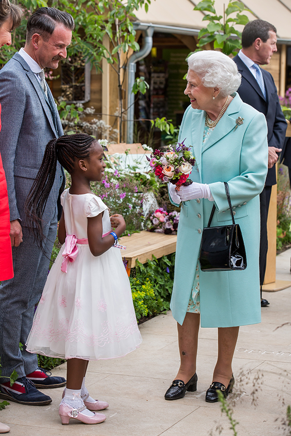 Chelsea Flower Show 2016, The Queen, Princess Beatrice and Princess Eugenie are presented with a bouquet of flowers by Angell Town resident Tavesha Steele 6 at the Green Grey Britainí Garden designed by Anne Marie Powell ....