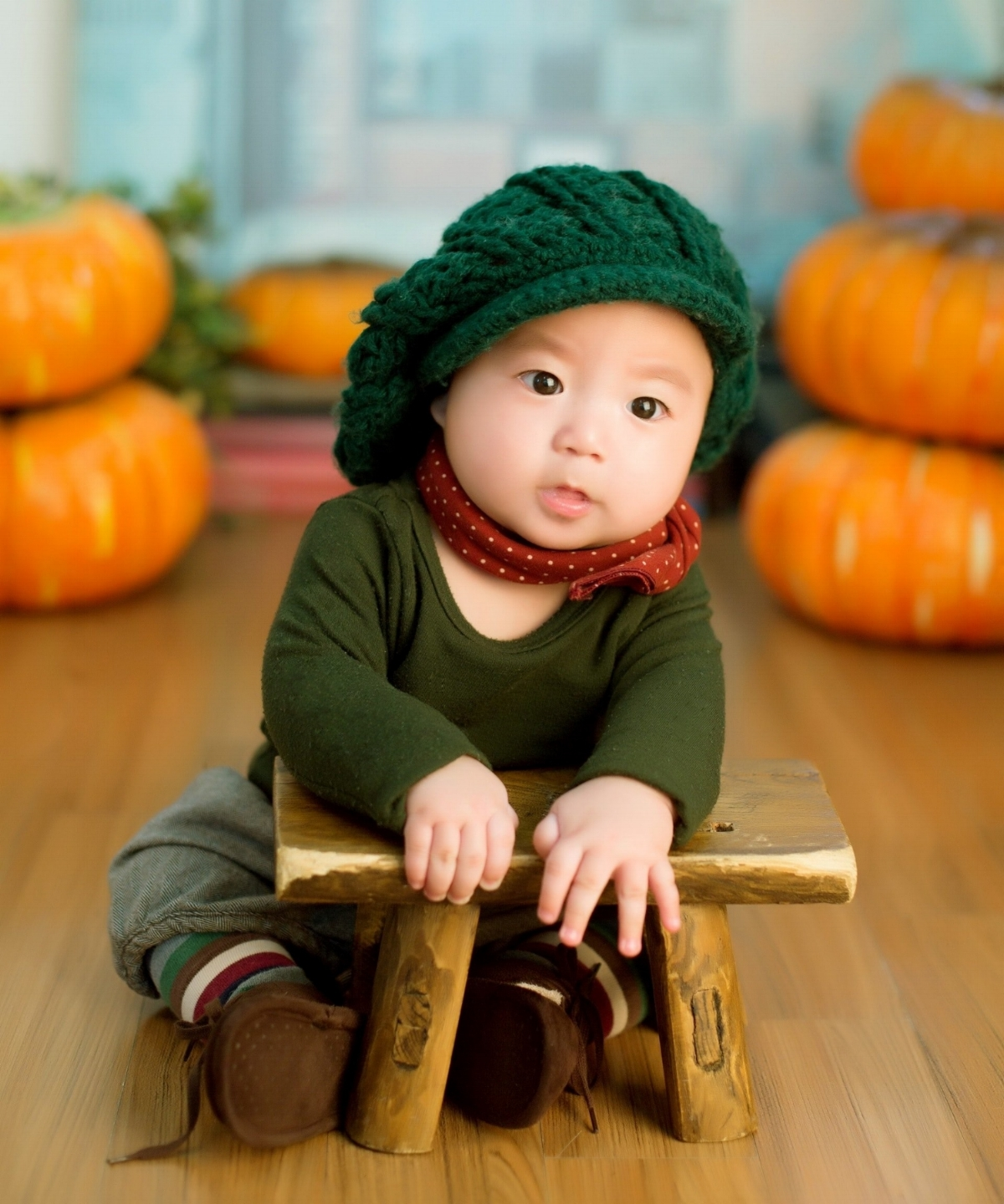 East Asian toddler wearing a green outfit and an oversized knitted hat, sits at a small wooden table in front of piles of pumpkins.