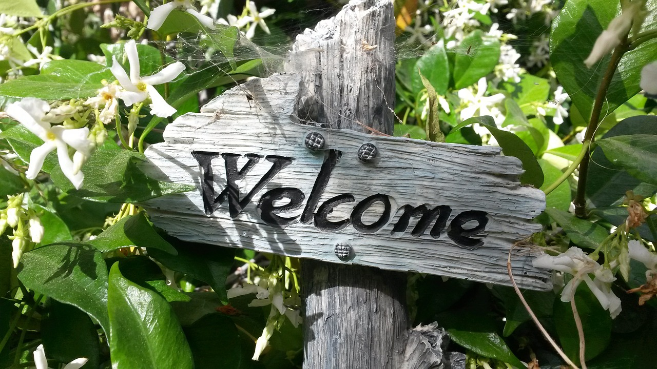 Rustic wooden welcome sign surrounded by jasmine leaves and flowers.