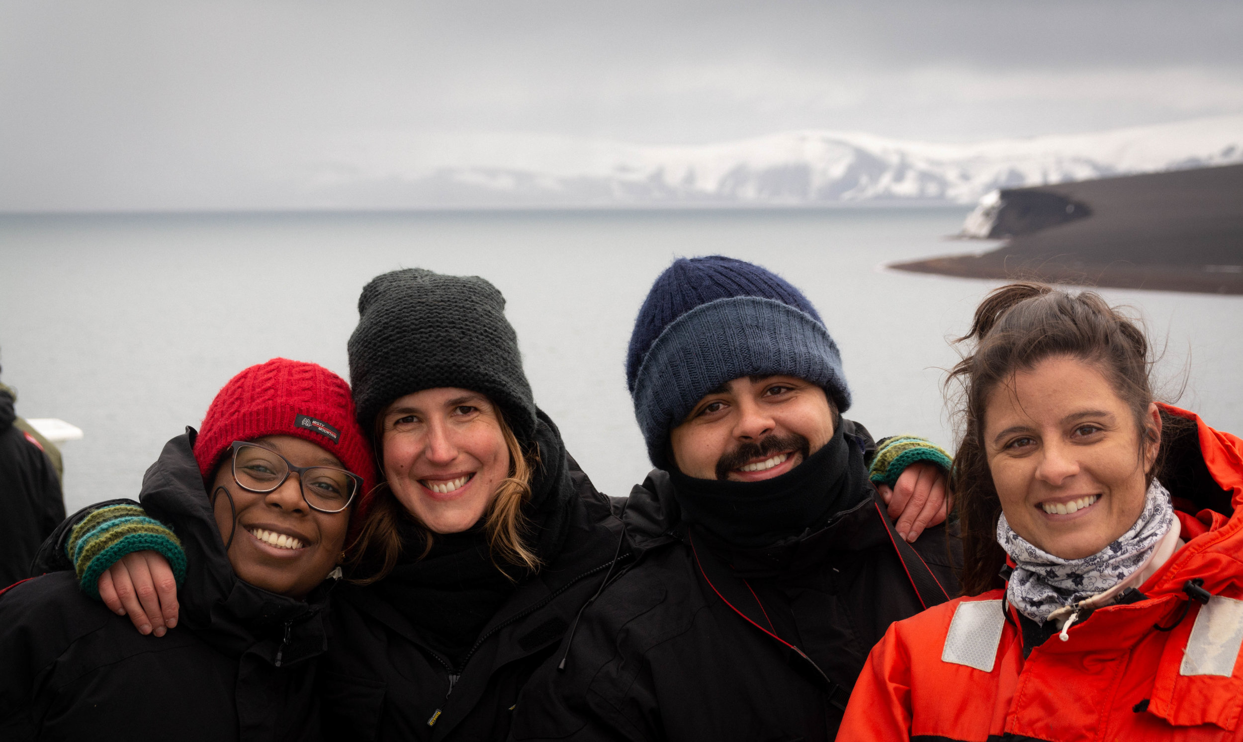 Happiness on board, with Deception Island in the background. From left to right: Raquel Avelina (oceanographer, State University of Rio de Janeiro), Catarina Guerreiro (Marine Geologist, MARE-FCiências.ID), Renan Lima (oceanographer, FURG) and Camila Signori (oceanographer, University of São Paulo).