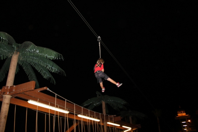 Image of a boy riding the sky wire at night.