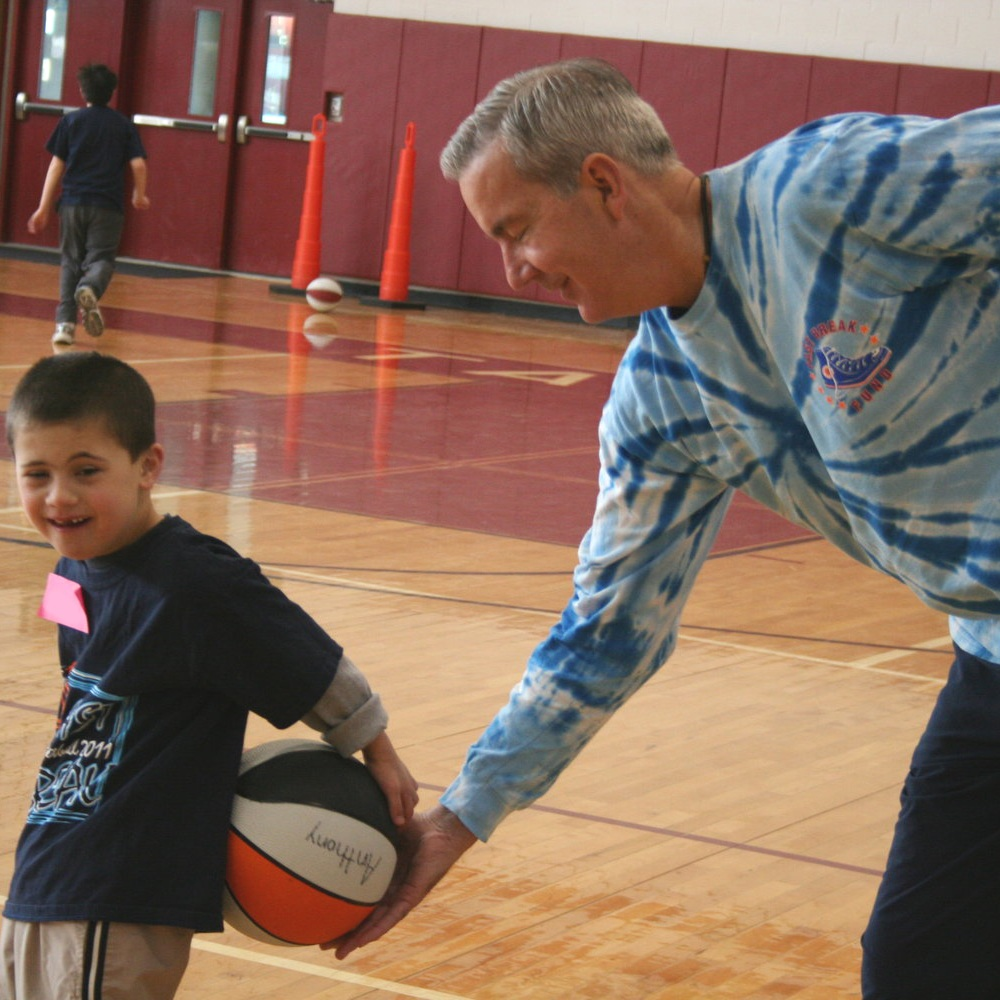 A man who volunteers for Fast Break Funds holding a basketball and smiling while standing next to a Fast Break Fund sports program participant.