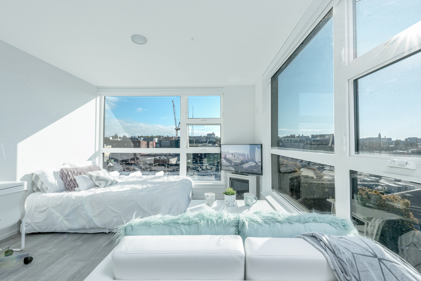 Studio bedroom at Pike Flats with large windows and white furniture
