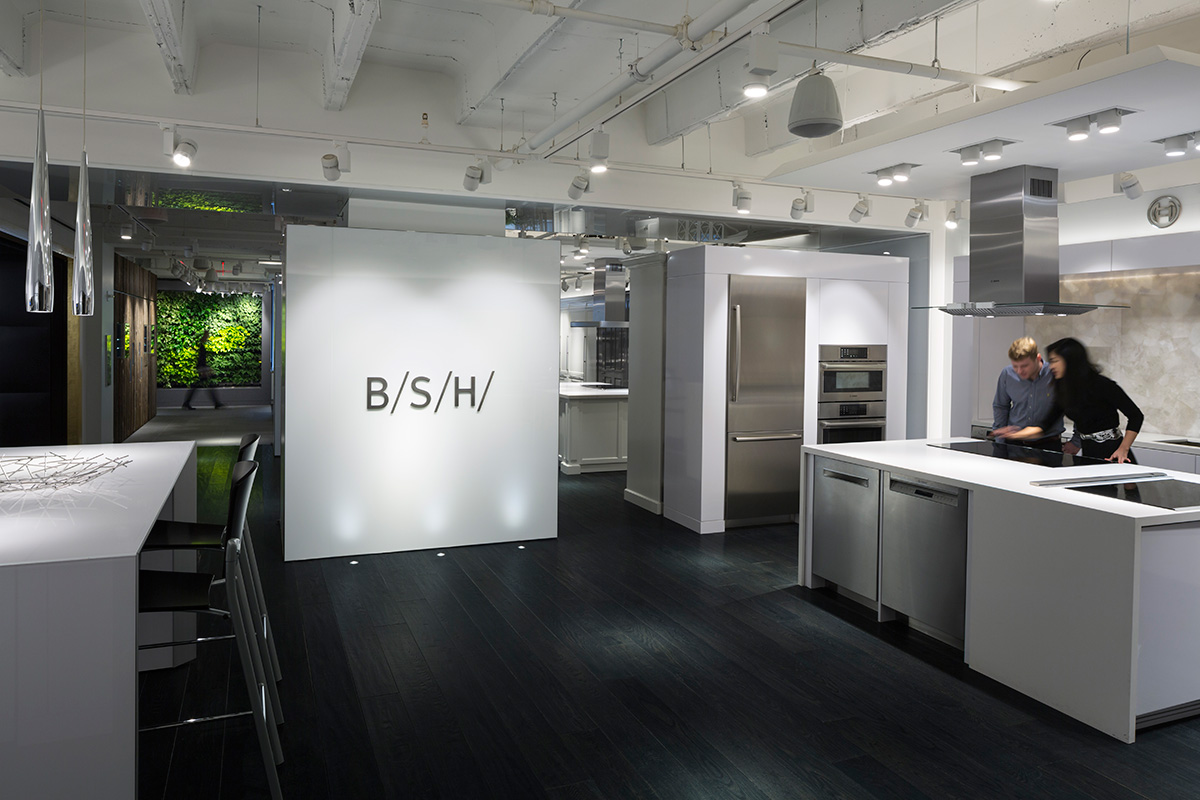 BSH logo displayed on a wall as a man and woman explore the showroom's kitchen space in New York. MEP provided by 2L Engineering.