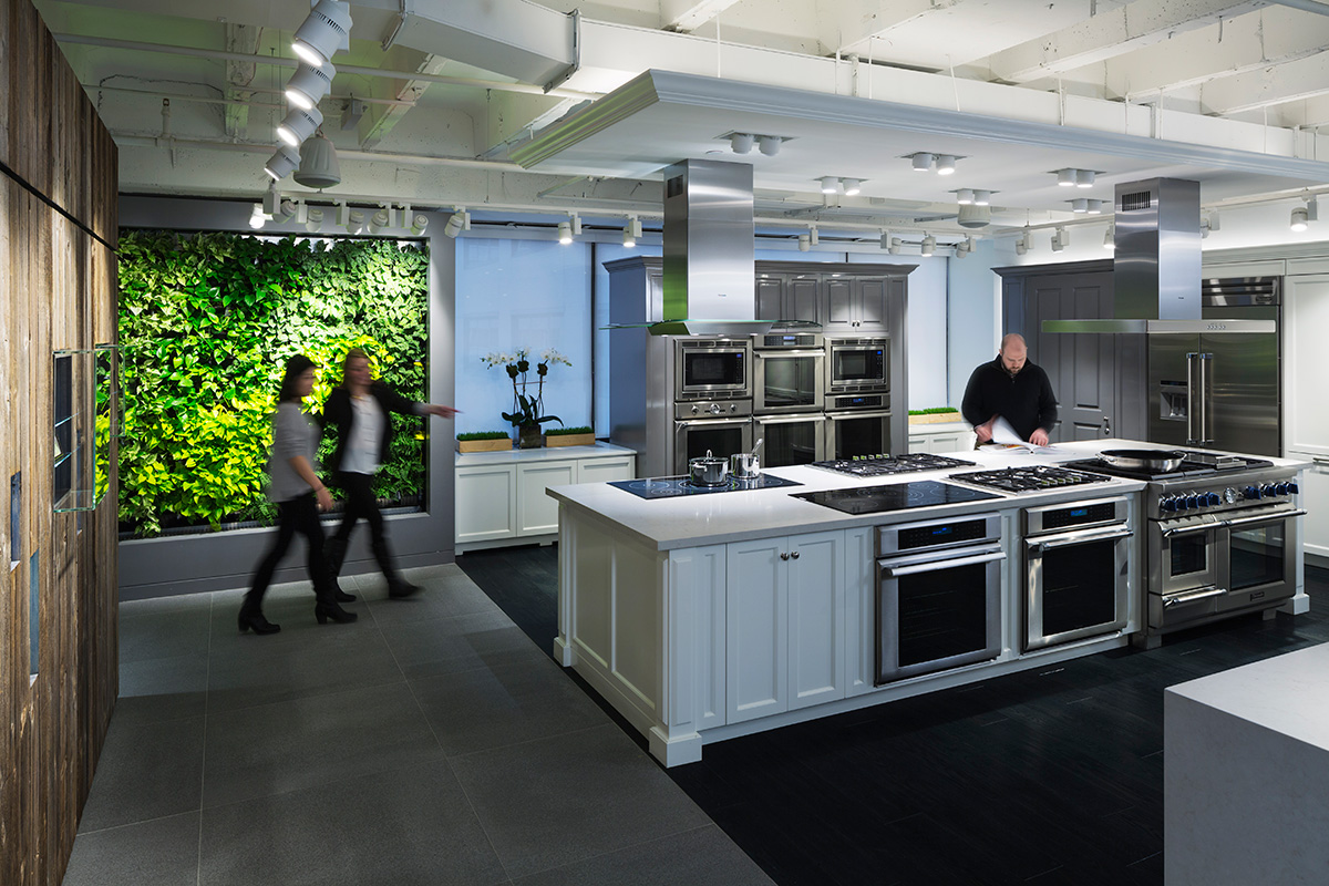 Two women walking by a green wall as a man reviews a catalog in a display kitchen in the BSH Showroom in New York. MEP provided by 2L Engineering.