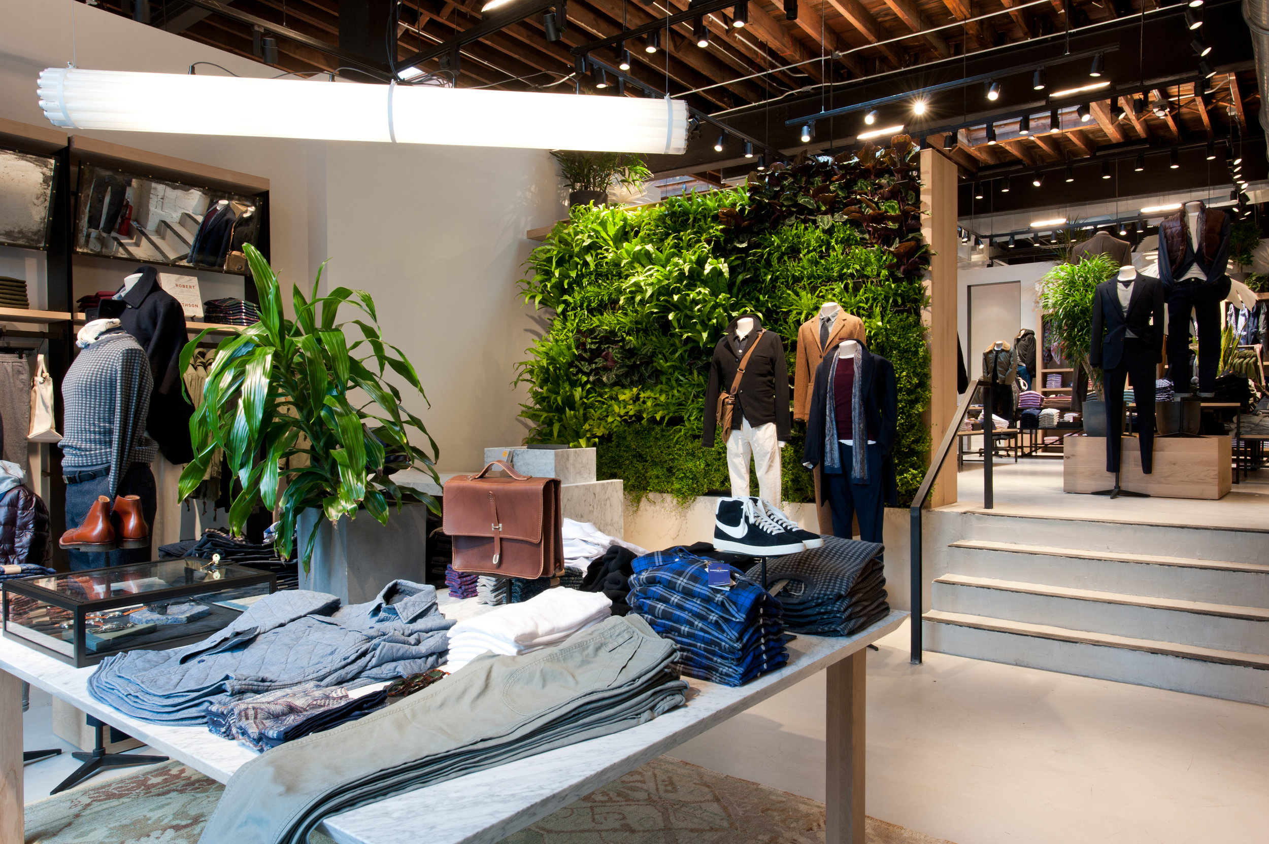 Folded display table with shoes, a bag, plants, and clothes in the contemporary interior of J Crew Williamsburg in Brooklyn, New York. MEP designed by 2L Engineering.