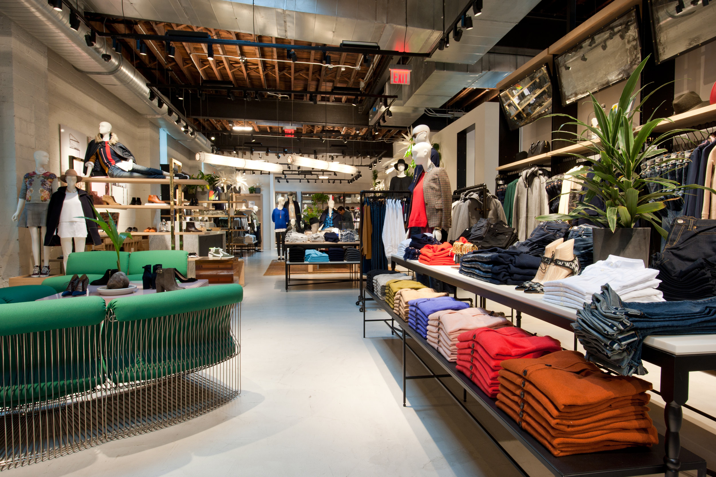 Mannequins in smart casual outfits, a shoe display, green couches, and folded shirts for customers to peruse in the Williamsburg location of J Crew. MEP by New York firm, 2L Engineering.