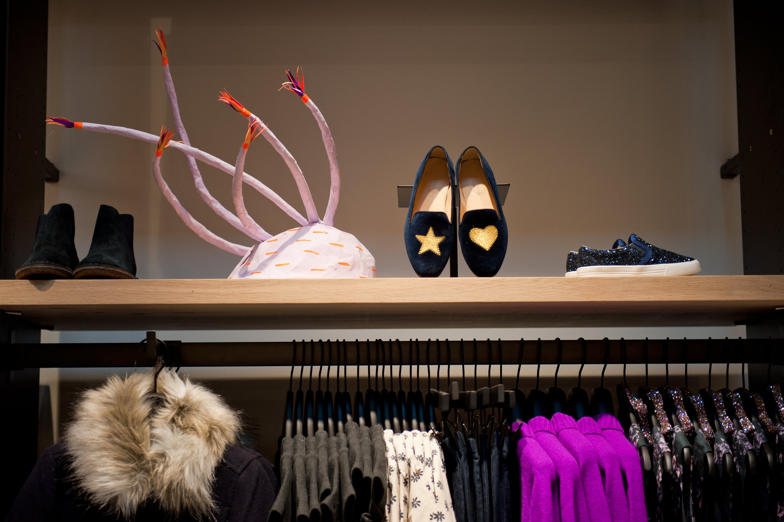 Loafers with a gold star and heart, sneakers, and booties beside a whimsical display over a clothing rack holding kid's outfits. MEP designed by 2L Engineering.