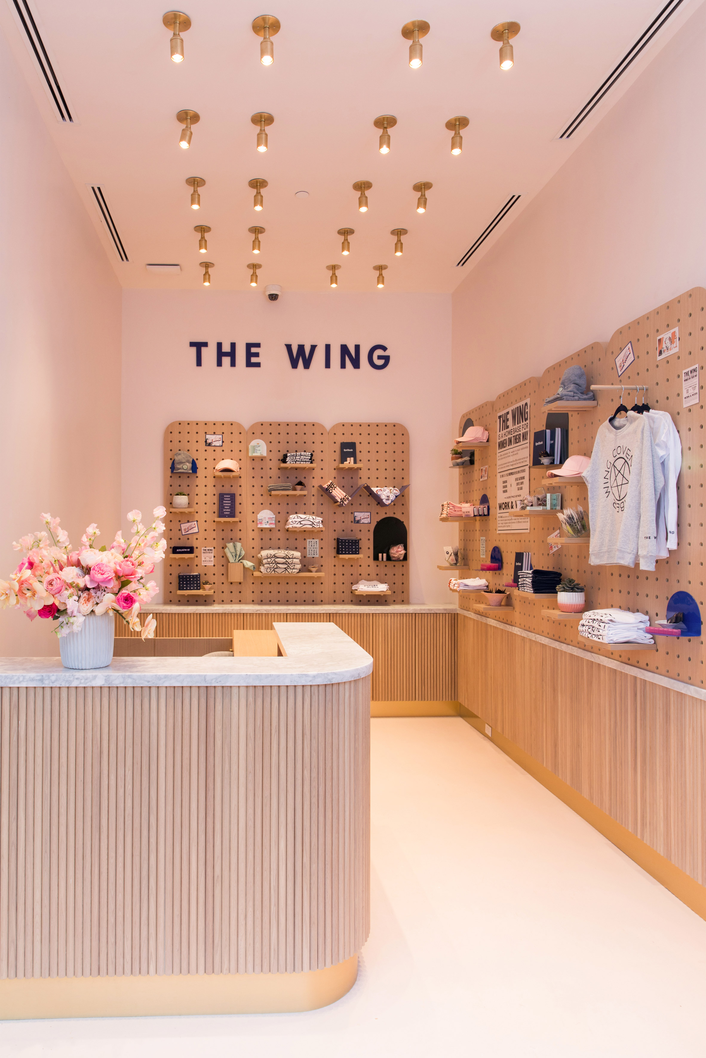 The checkout and retail area of The Wing Dumbo, featuring brand merchandise mounted on a pegboard. MEP Engineering provided by 2L Engineering.