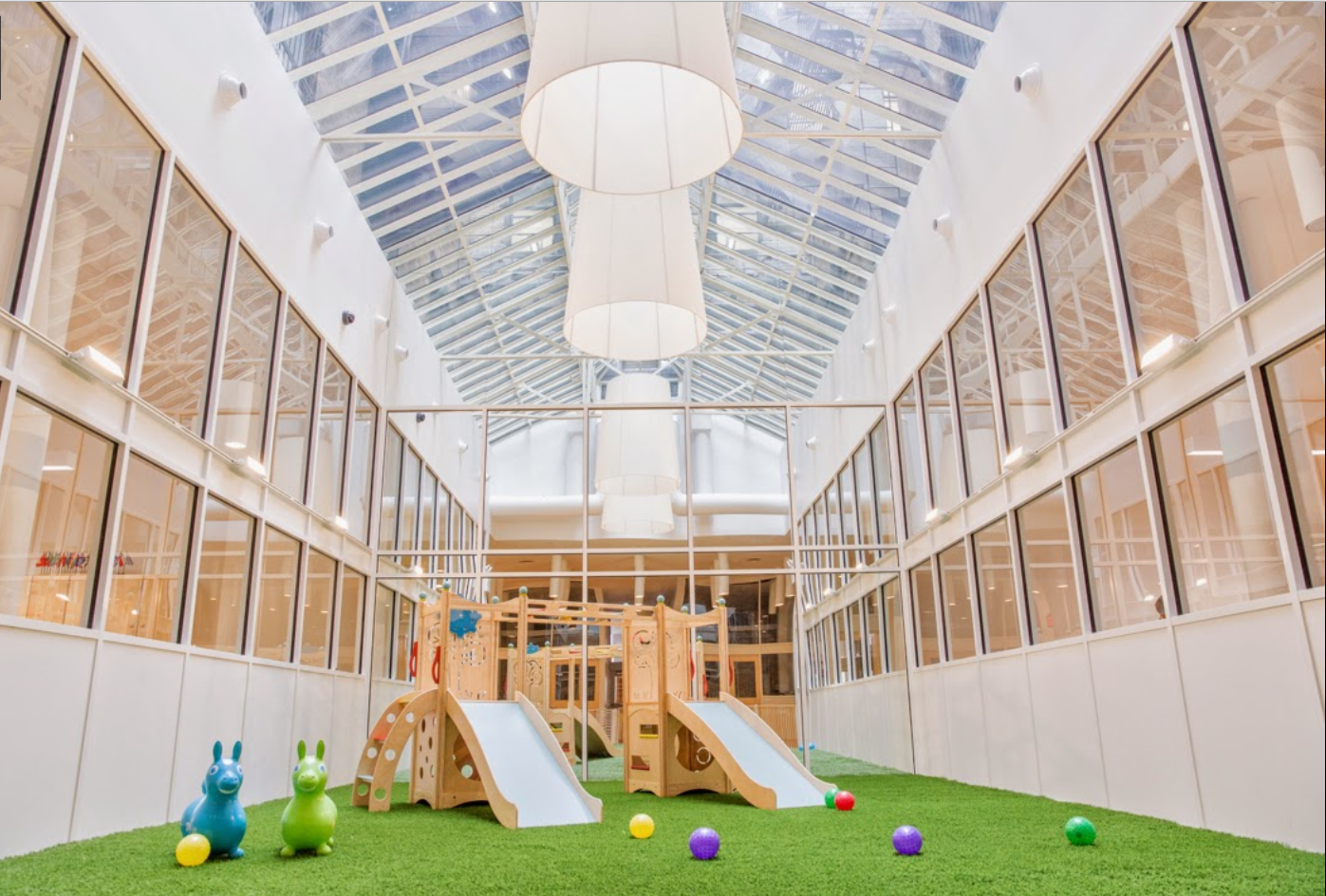 Brightly lit playroom with slides and an inside playground at the Flatiron location of the Montessori School. MEP Engineering provided by 2L Engineering.