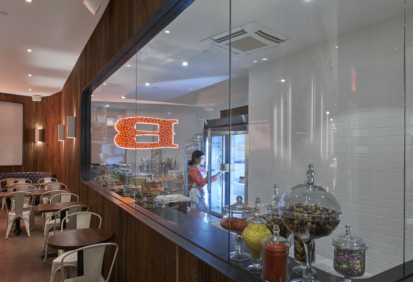 Viewing window to the kitchen of Baked Tribeca where a worker places a cake inside a bright refrigerator; the large B reflected on the glass. MEP designed by 2L Engineering.