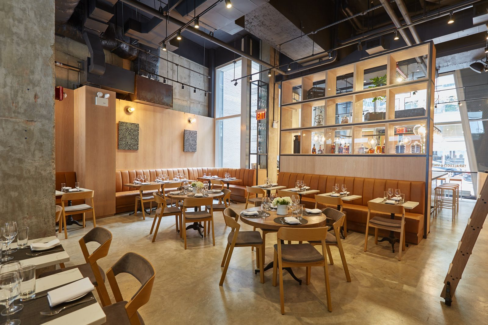 Indoor seating with warm tones and a large decorative shelf inside Tarallucci e Vino in New York. MEP provided by 2L Engineering.