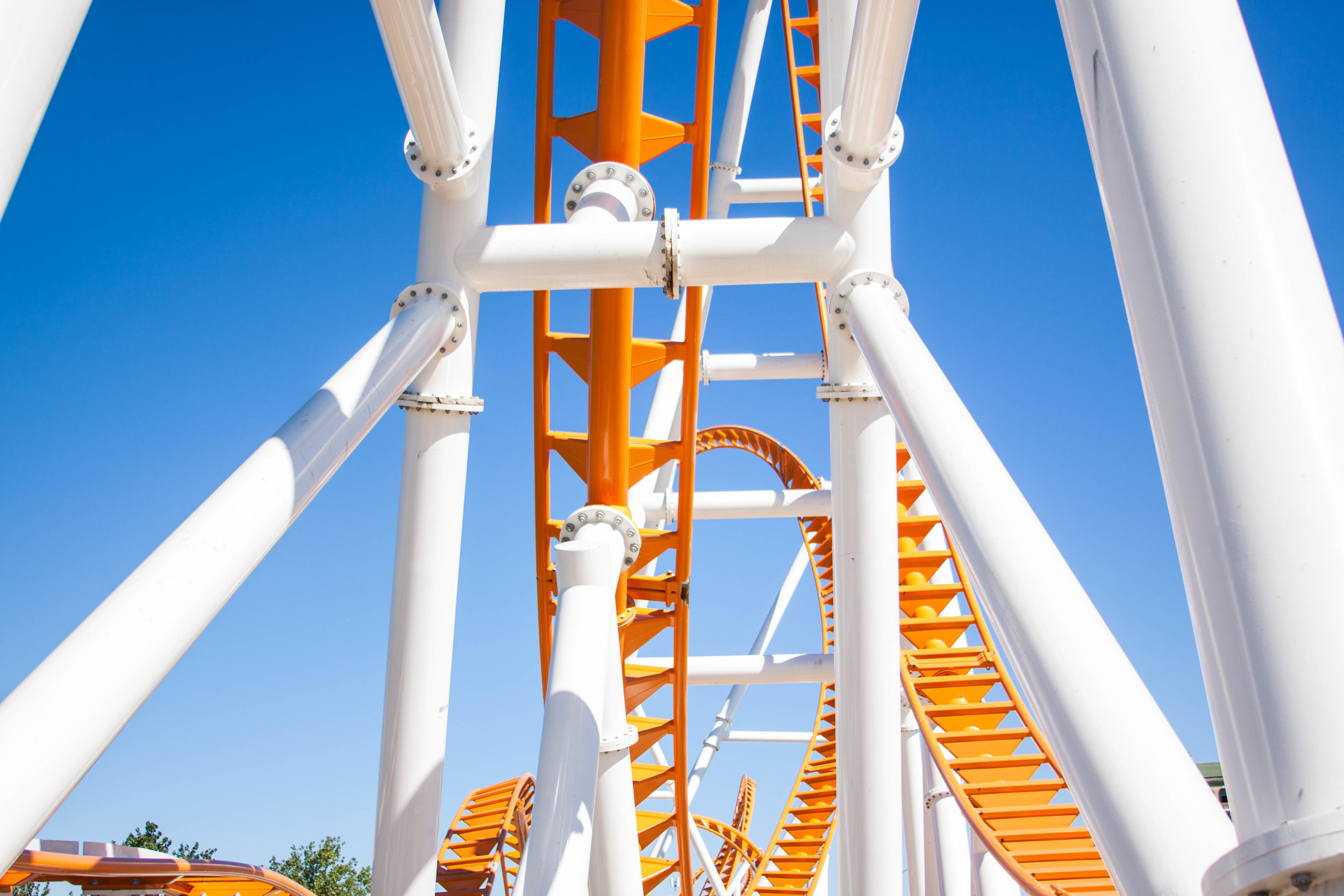 Under view of the Thunderbolt Rollercoaster with it's orange tracks and white support structure in the bright sunlight at Brooklyn's Coney Island. MEP designed by 2L Engineering.