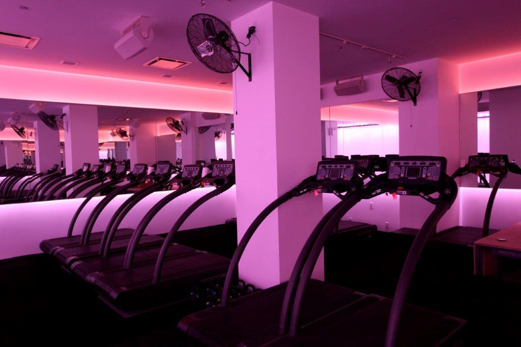 Pink lit room with multiple treadmills a mirrors with backlights mounted on the walls in the Mile High Run Club, with MEP designed by 2L Engineering.