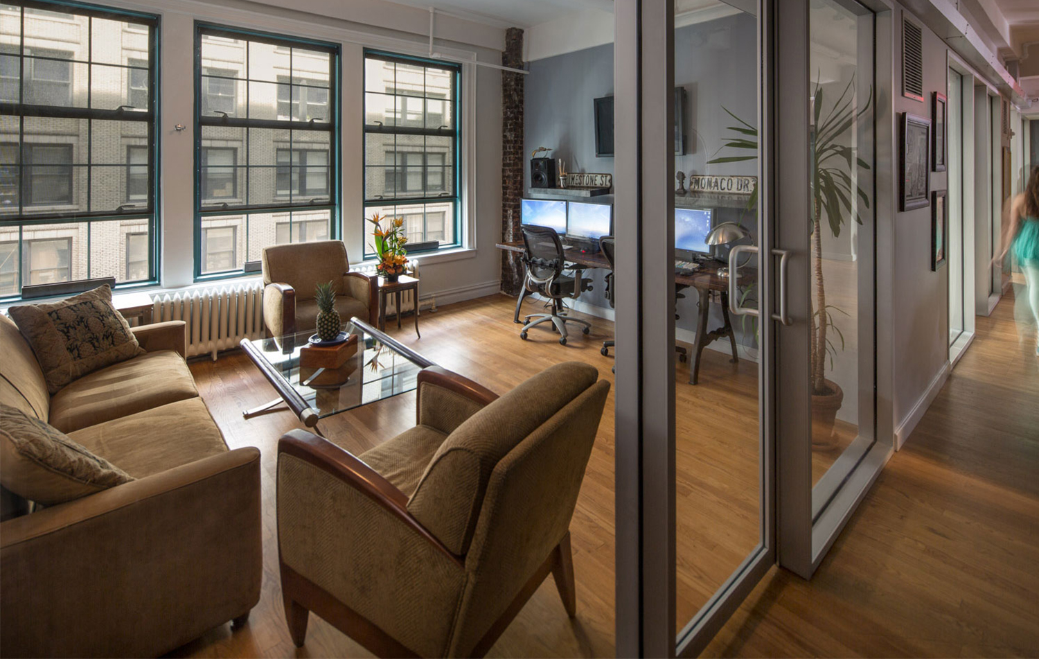 Office space with road signs, large windows, and a lounge area with a pineapple centerpiece in the offices of Napoleon studios, Brooklyn. MEP by 2L Engineering..