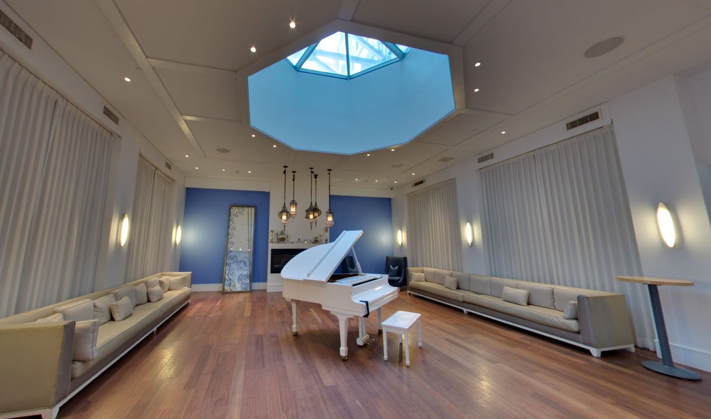 White grand piano under a skylight in with a light bluish purple accent wall and large couches for guests to sit and enjoy music. MEP designed by 2L Engineering..
