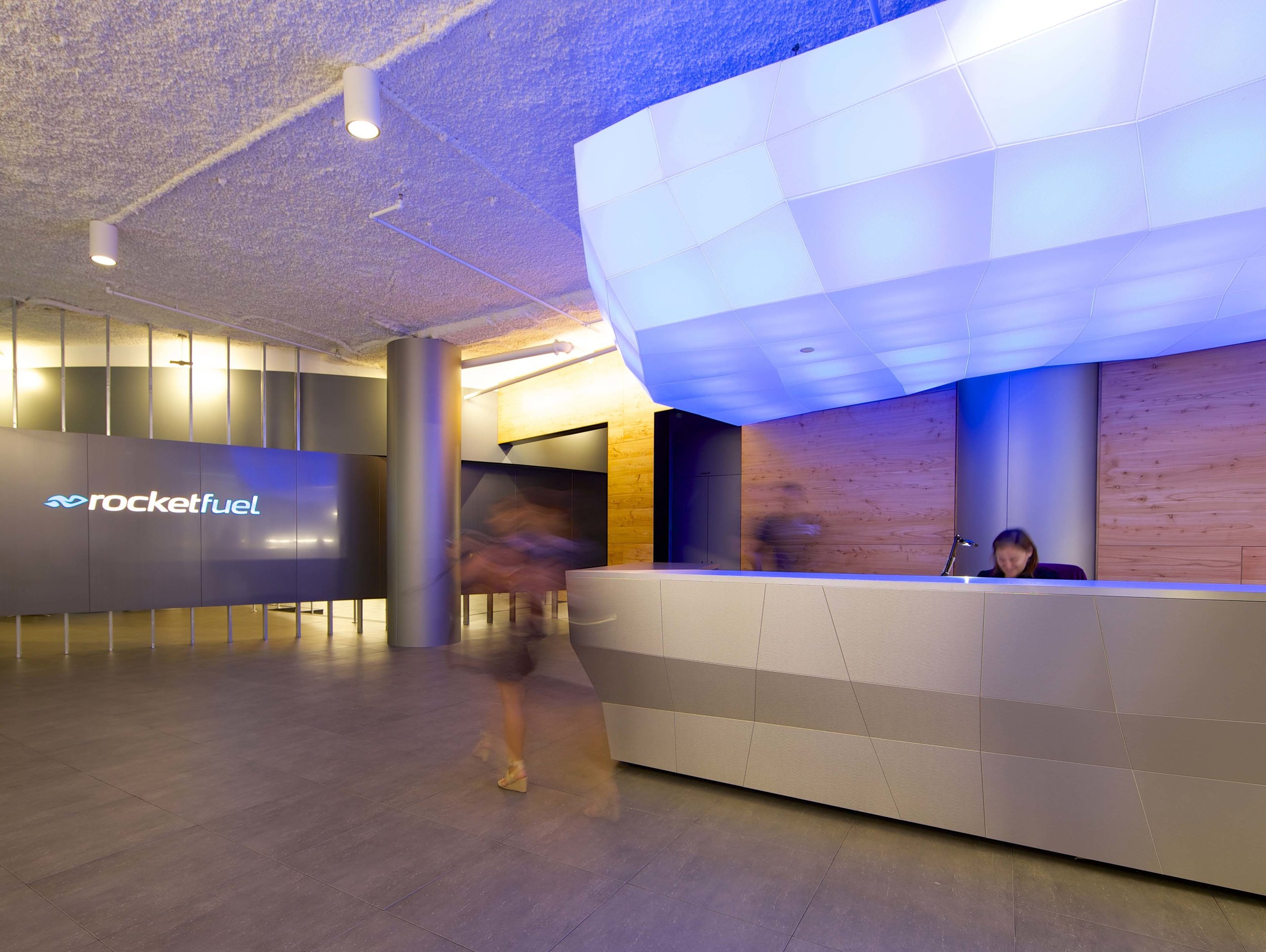 Reception area with a woman behind the desk and blue lighting at Rocketfuel headquarters. MEP by 2L Engineering.