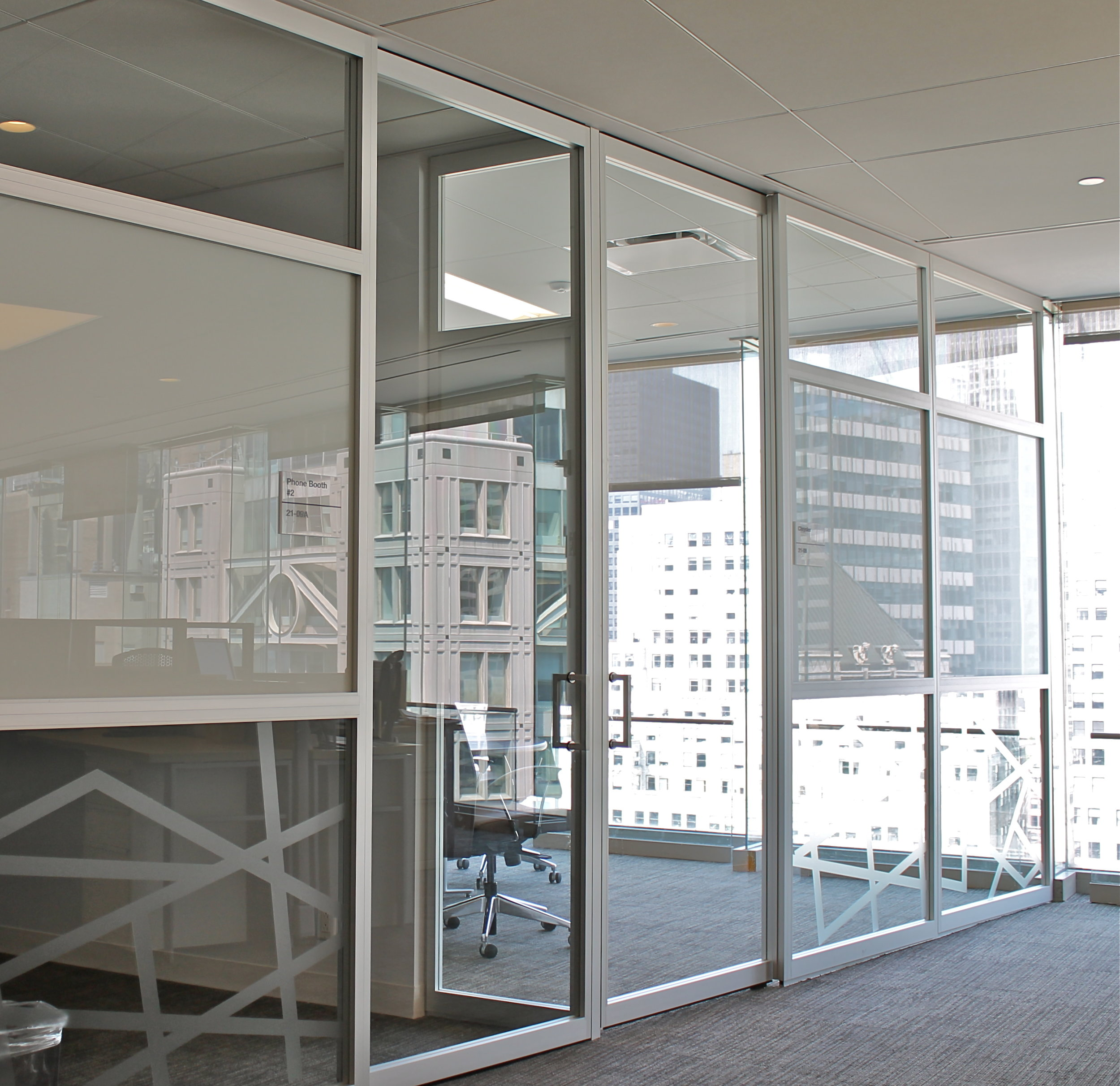 The city reflected on glass paneling with frosted glass accents looking into a conference room at Wood Mackenzie offices. MEP design by 2L Engineering.