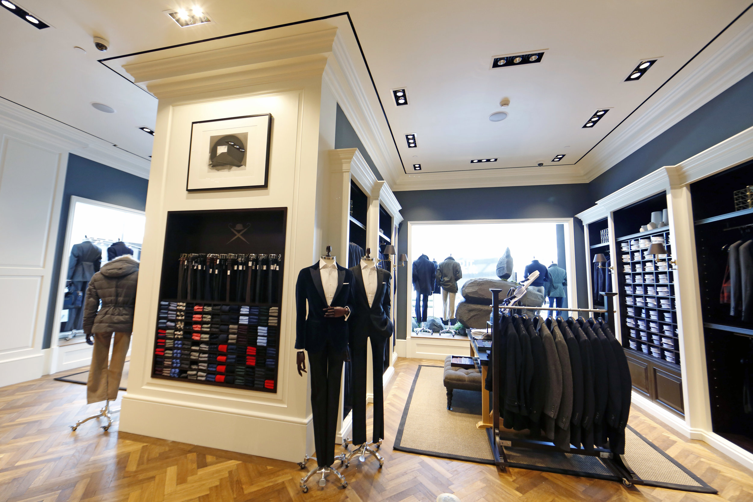 Belt and necktie display shelf beside suited up mannequins and a clothing rack of blazers in Hackett London, Woodbury Common Premium Outlet, New York. MEP designed by 2L Engineering